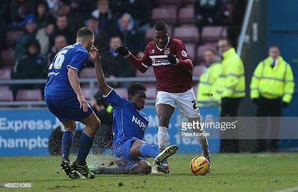 Antonio German of Northampton Town attempts to move forward with the ball under pressure from Armand Gnanduillet and Dan Gardner of Chesterfield...