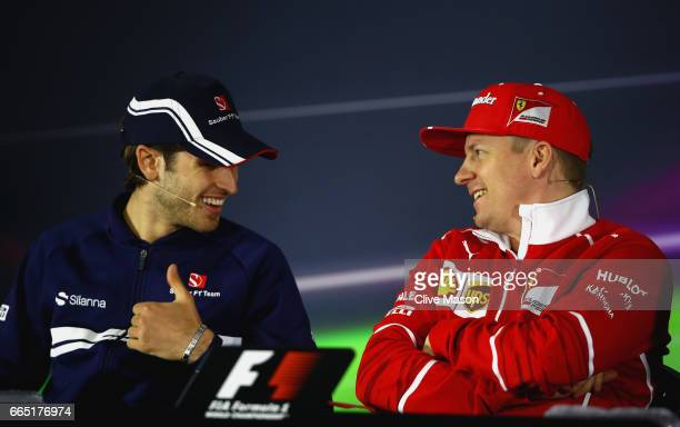 Antonio Giovinazzi of Italy and Sauber F1 and Kimi Raikkonen of Finland and Ferrari talk in the Drivers Press Conference during previews to the...