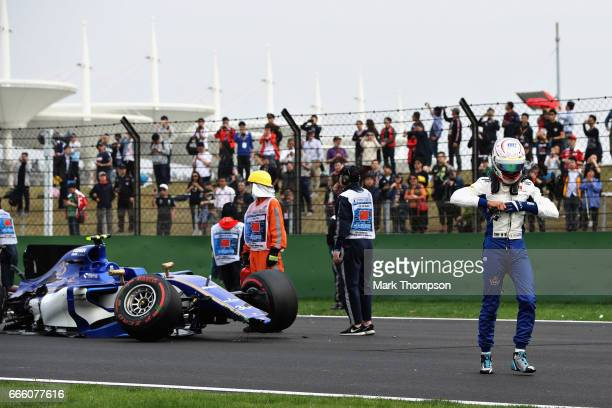 Antonio Giovinazzi of Italy and Sauber F1 walks from the wreckage of his car after crashing during qualifying for the Formula One Grand Prix of China...