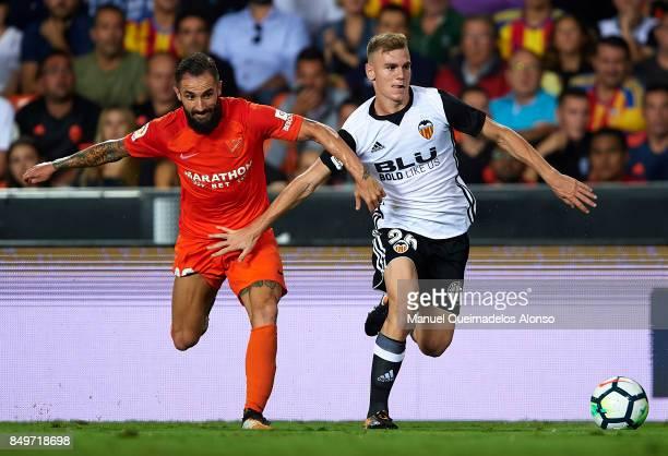 Antonio Latorre Lato of Valencia competes for the ball with Cifuentes of Malaga during the La Liga match between Valencia and Malaga at Estadio...