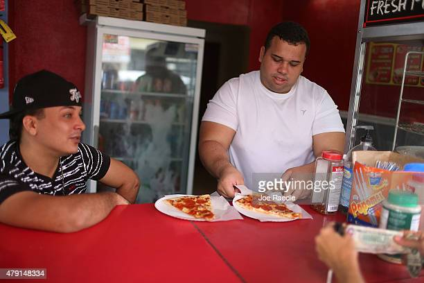 Antonio Lopez sells pizza to a customer on July 1 2015 in San Juan Puerto Rico The island's residents are dealing with increasing economic hardships...