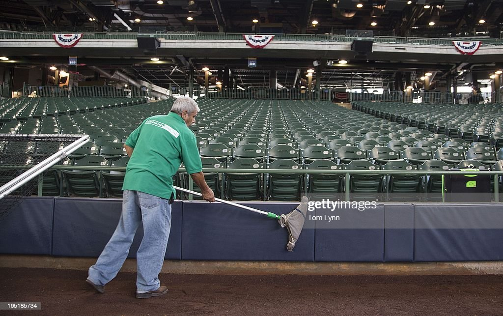 Antonio Medina cleans the wall on the first base line before the start of the game between the Milwaukee Brewers and Colorado Rockies on opening day at Miller Park on April 1, 2013 in Milwaukee, Wisconsin.