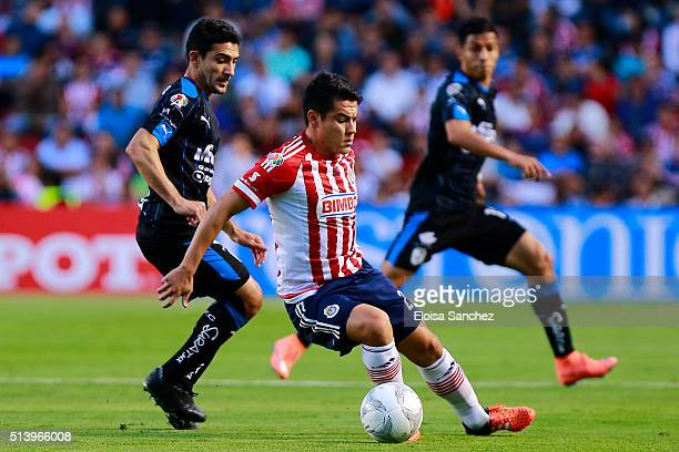 Antonio Naelson of Queretaro struggles for the ball with Michael Perez of Chivas during the 9th round match between Queretaro and Chivas as part of...