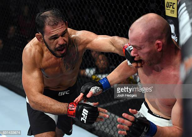 Antonio Rogerio Nogueira of Brazil punches Patrick Cummins in their light heavyweight bout during the UFC 198 event at Arena da Baixada stadium on...