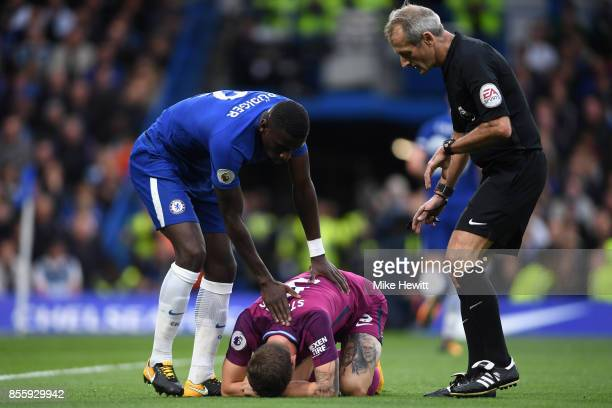 Antonio Rudiger of Chelsea checks if John Stones of Manchester City is okay as referee Martin Atkinson comes over during the Premier League match...