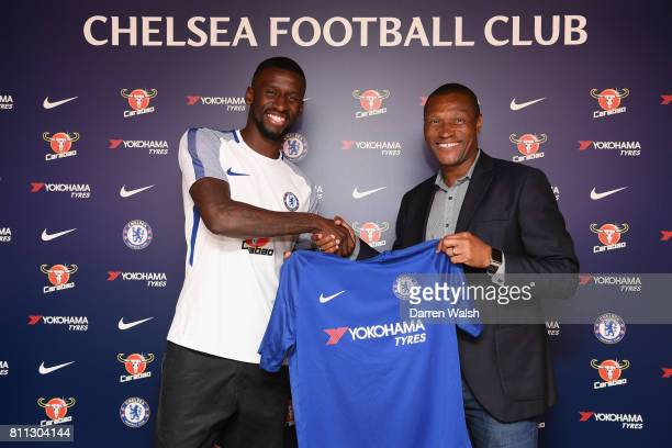 Antonio Rudiger of Chelsea holds his shirt with Technical Director of Chelseaa Michael Emenalo after signing a 5 year contract at Chelsea Training...