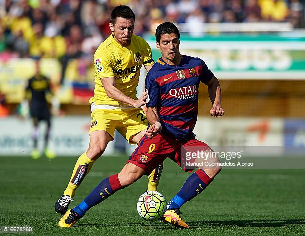 Antonio Rukavina of Villarreal competes for the ball with Luis Suarez of Barcelona during the La Liga match between Villarreal CF and FC Barcelona at...