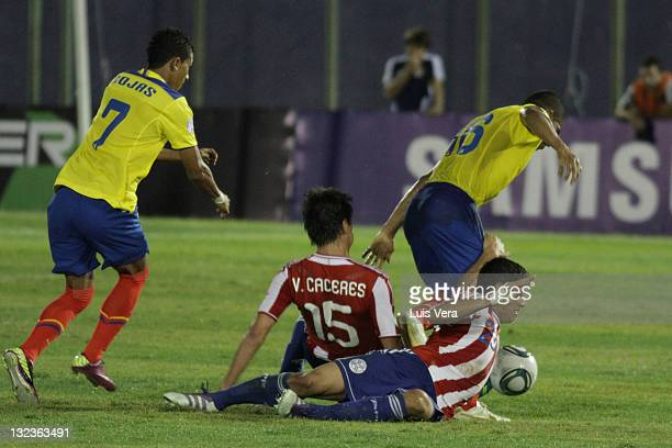 Antonio Valencia and Joao Rojas from Ecuador conducts the ball with Victor Caceres and Richard Ortiz from Paraguay during a match between Paraguay...