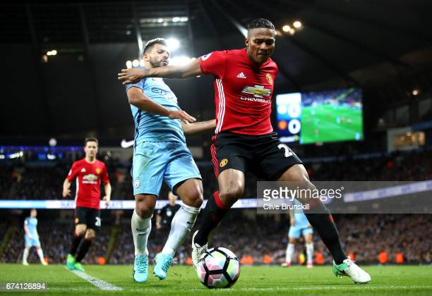 Antonio Valencia of Manchester United holds off Sergio Aguero of Manchester City during the Premier League match between Manchester City and...