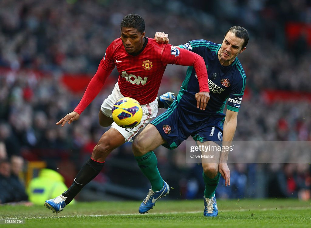 Antonio Valencia of Manchester United is challenged by John O'Shea of Sunderland during the Barclays Premier League match between Manchester United and Sunderland at Old Trafford on December 15, 2012 in Manchester, England.