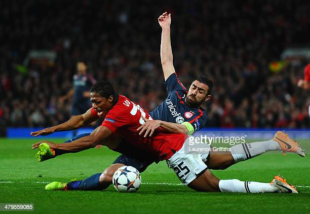 Antonio Valencia of Manchester United tangles with Giannis Maniatis of Olympiacos during the UEFA Champions League Round of 16 second round match...