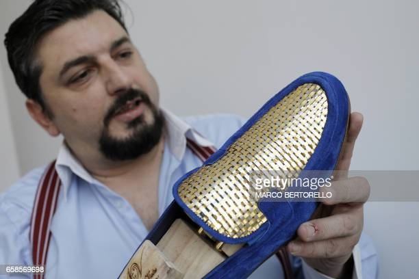 Antonio Vietri artisan and founder of AV Fashion shows a man shoe as part of his collection 'Gold' on March 16 2017 in his workshop in Turin Antonio...