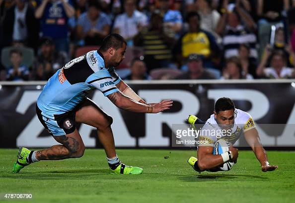 Antonio Winterstein of the Cowboys scores a try despite the defence of Andrew Fifita of the Sharks during the round 16 NRL match between the North...