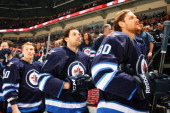 Antti Miettinen Eric Tangradi and Nik Antropov of the Winnipeg Jets stand on the bench during the singing of the National anthem prior to puck drop...