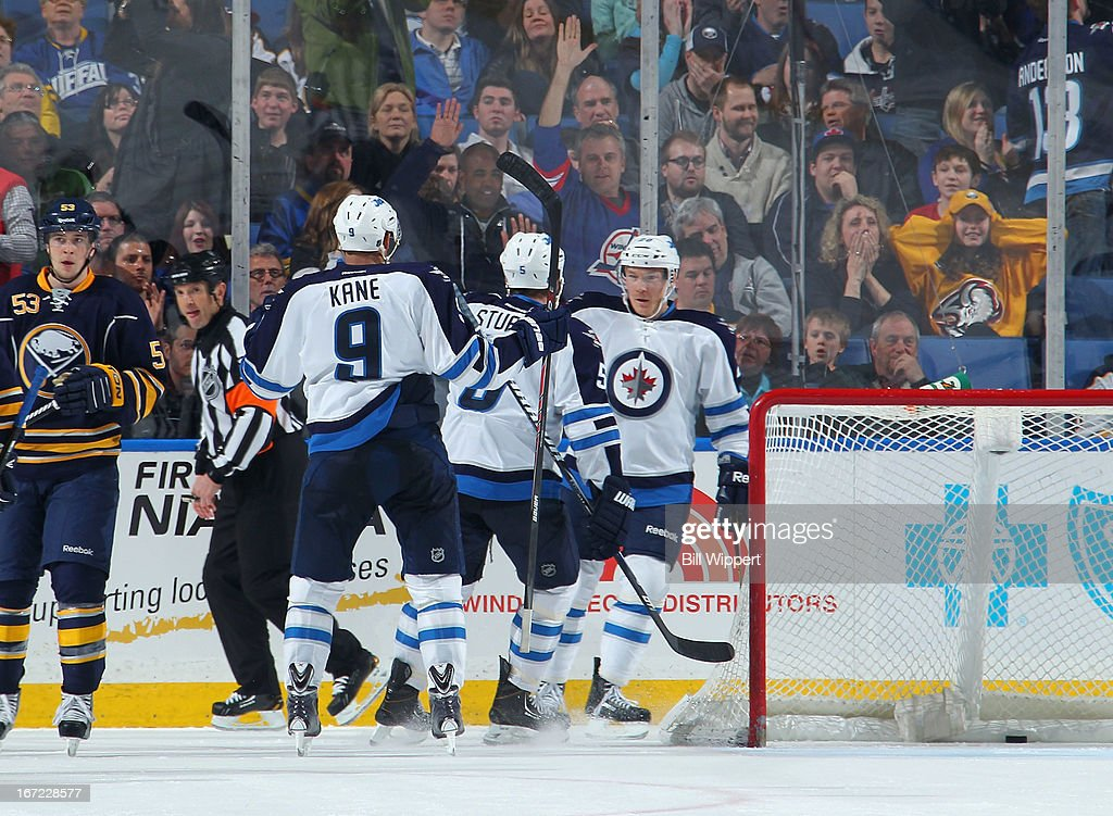 Antti Miettinen #20 (R) of the Winnipeg Jets celebrates with teammates Evander Kane #9 and Mark Stuart #5 after scoring the winning goal against the Buffalo Sabres on April 22, 2013 at the First Niagara Center in Buffalo, New York. Winnipeg defeated Buffalo, 2-1.