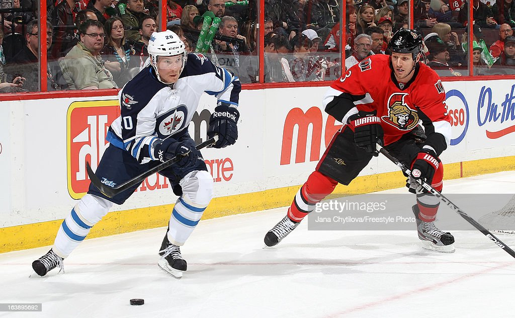Antti Miettinen #20 of the Winnipeg Jets skates with the puck against Marc Methot #3 of the Ottawa Senators, during an NHL game at Scotiabank Place, on March 17, 2013 in Ottawa, Ontario, Canada.