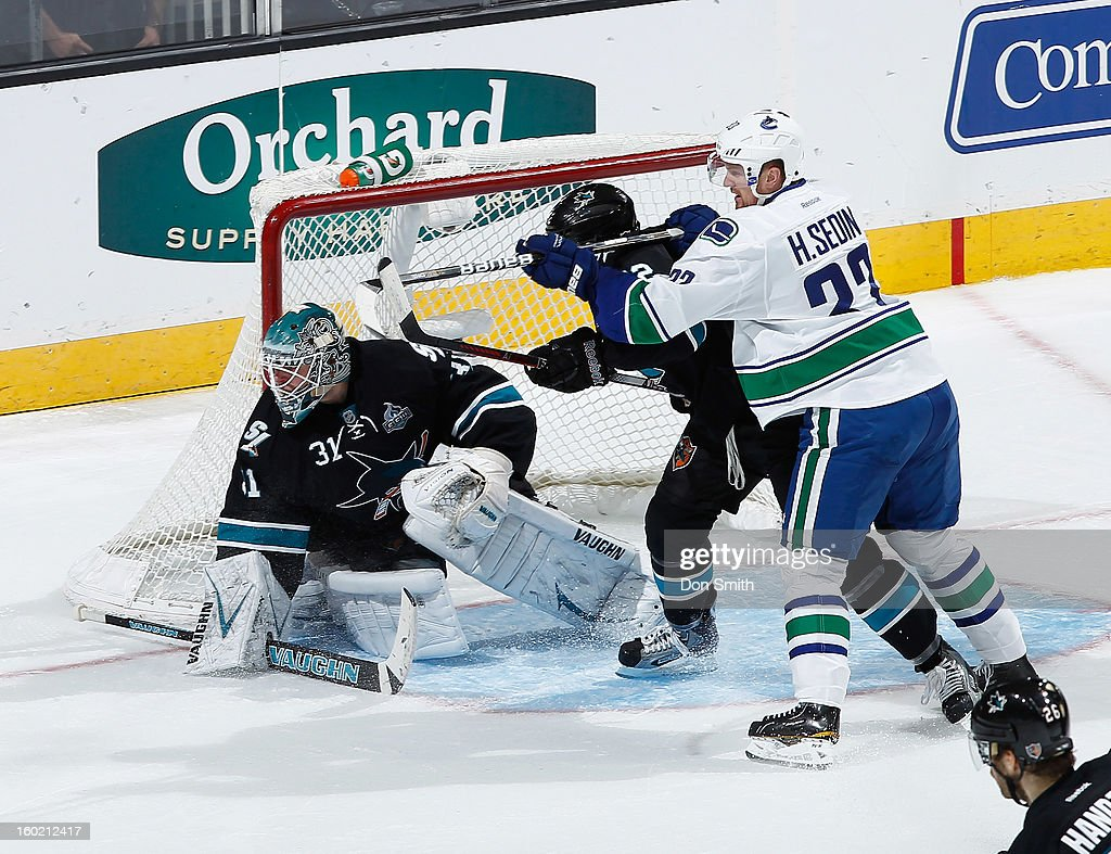 Antti Niemi #31 and Dan Boyle #22 of the San Jose Sharks protect the net against Henrik Sedin #33 of the Vancouver Canucks during an NHL game on January 27, 2013 at HP Pavilion in San Jose, California.