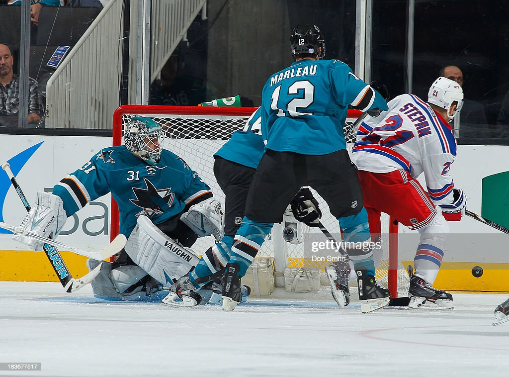Antti Niemi #31 and Patrick Marleau #12 of the San Jose Sharks protect the net against Derek Stepan #21 of the New York Rangers during an NHL game on October 8, 2013 at SAP Center in San Jose, California.