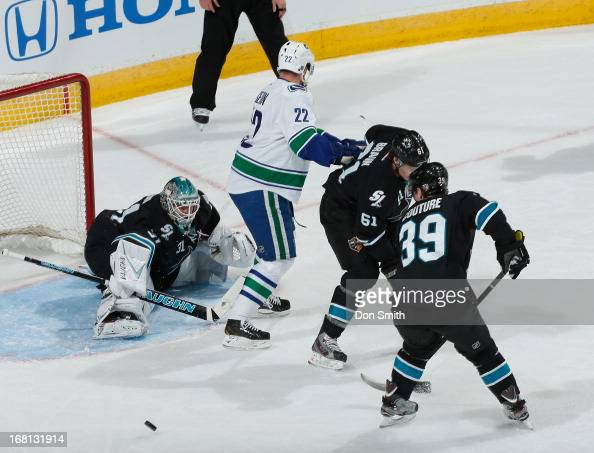 Antti Niemi Logan Couture and Justin Braun of the San Jose Sharks defend the net against Daniel Sedin of the Vancouver Canucks in Game One of the...
