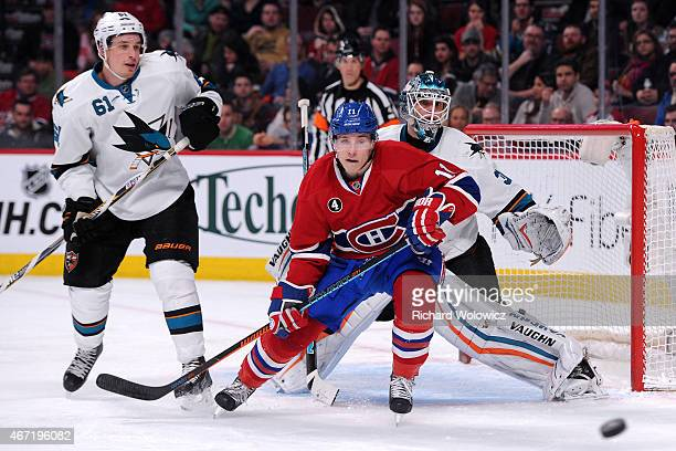 Antti Niemi of the San Jose Sharks and Brendan Gallagher of the Montreal Canadiens watch the incoming puck during the NHL game at the Bell Centre on...