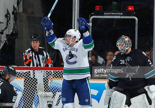 Antti Niemi of the San Jose Sharks watches as Alexandre Burrows of the Vancouver Canucks celebrates his third period goal in Game Four of the Western...