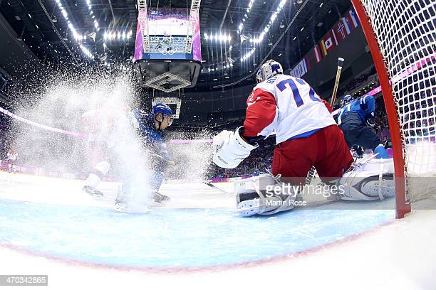 Antti Pihlstrom of Finland tries to control the puck against Sergei Bobrovski of Russia during the Men's Ice Hockey Quarterfinal Playoff on Day 12 of...