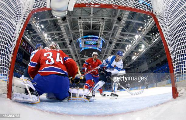 Antti Pihlstrom of Finland tries to handle the puck in front of Lars Volden of Norway in the second period during the Men's Ice Hockey Preliminary...