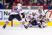 Antti Raanta of the Chicago Blackhawks makes a save as Michal Rozsival of the Chicago Blackhawks attempts to block the shot during the game against...