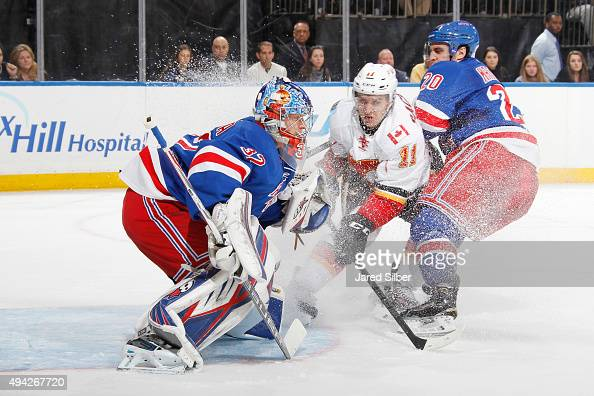 Antti Raanta of the New York Rangers tracks the puck as Ryan McDonagh of the New York Rangers and Mikael Backlund of the Calgary Flames crash the net...