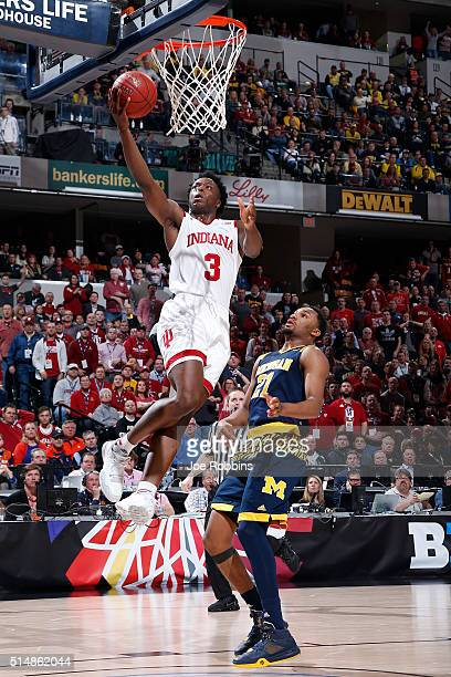 Anunoby of the Indiana Hoosiers drives past Zak Irvin of the Michigan Wolverines after getting a steal in the quarterfinal round of the Big Ten...