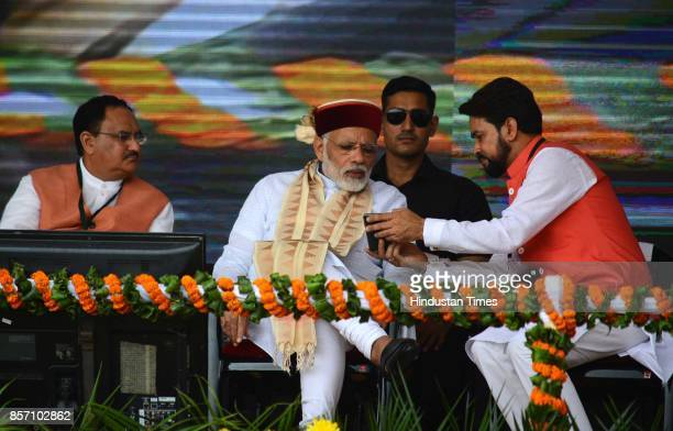 Anurag Thakur shows something to Prime Minister Narendra Modi on his mobile during a BJP Abhar Rally at Luhnu ground on October 3 2017 in Bilaspur...