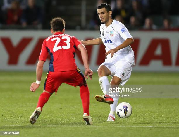 Anvar Gafurov of Bunyodkor passes the ball past Evan Kostopoulos of Adelaide during the AFC Champions League Quarter Final match between Adelaide...