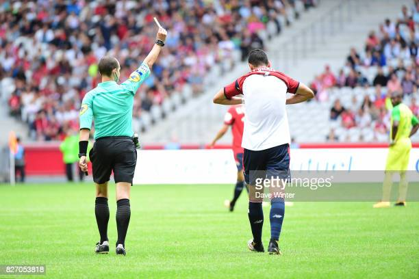 Anwar El Ghazi of Lille receives a yellow card from referee Benoit Millot for removing his shirt when celebrating his goal during the Ligue 1 match...