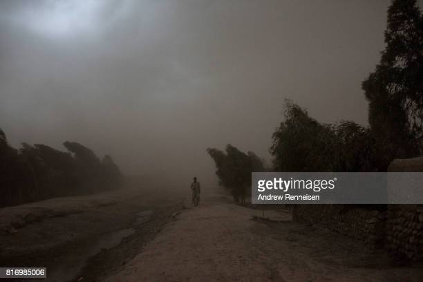 Anwar Pachir whose family was displaced by the Islamic State of Iraq and Syria Khorasan walks through a storm outside his current home on July 14 in...