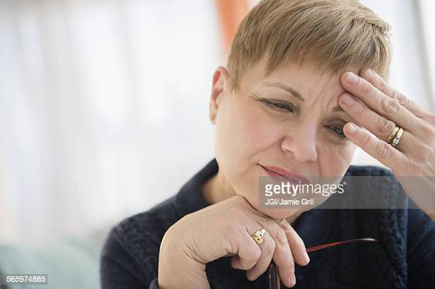 Anxious Caucasian woman rubbing forehead