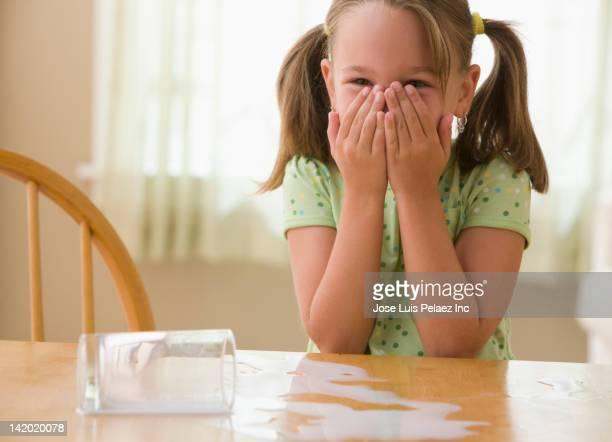 Anxious girl spilling milk