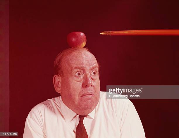 Anxious man looking at arrow directed at apple on top of his head. (Photo by H. Armstrong Roberts/Retrofile/Getty Images)