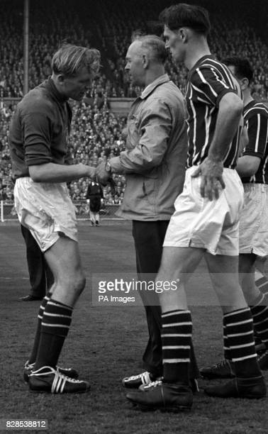 Anxious Manchester City players rush to the aid of their Germanborn goalkeeper Bert Trautmann injured in a collision with Birmingham City's inside...