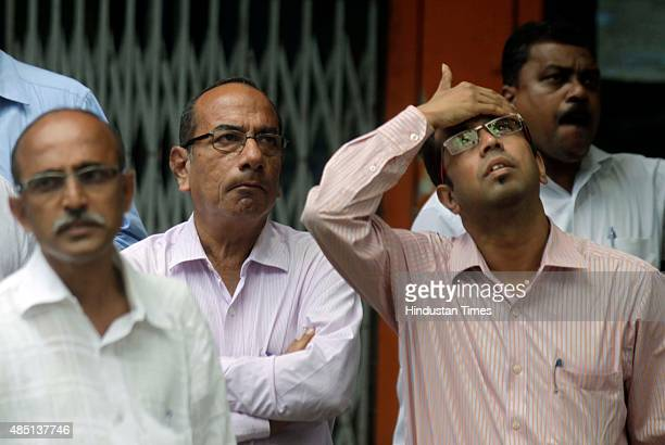 Anxious onlookers watch share prices on a screen outside the Bombay Stock Exchange on August 24 2015 in Mumbai India Sensex crashed over 1700 points...
