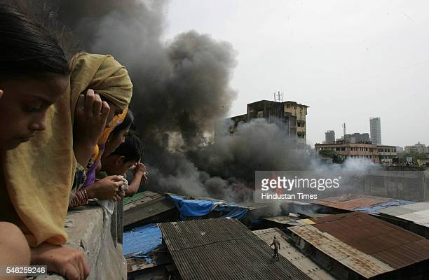 Anxious residents watch as flames rise from an iron godown that caught fire near Kamathipura