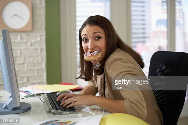 Anxious Woman Eating While Working on Her Computer
