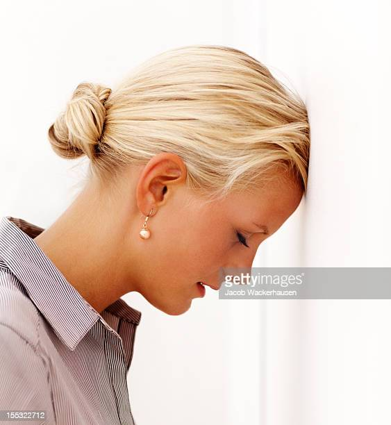 Anxious young lady leaning head on a wall