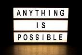Anything is possible light box sign board on wooden table.