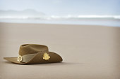 A close up of an Australian army slouch hat sitting on the sand of a beach with plenty of copyspace for your words
