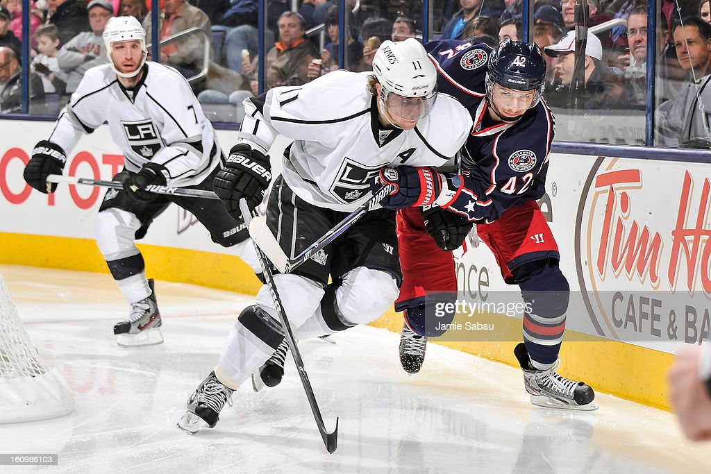 Anze Kopitar #11 of the Los Angeles Kings and Artem Anisimov #42 of the Columbus Blue Jackets battle for position on a loose puck on February 5, 2013 at Nationwide Arena in Columbus, Ohio.