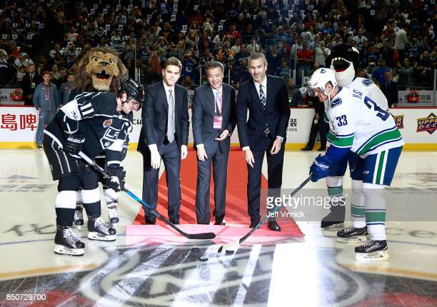 Anze Kopitar of the Los Angeles Kings and Henrik Sedin of the Vancouver Canucks take a ceremonial faceoff from Luc Robitaille Sun Weimin and Trevor...