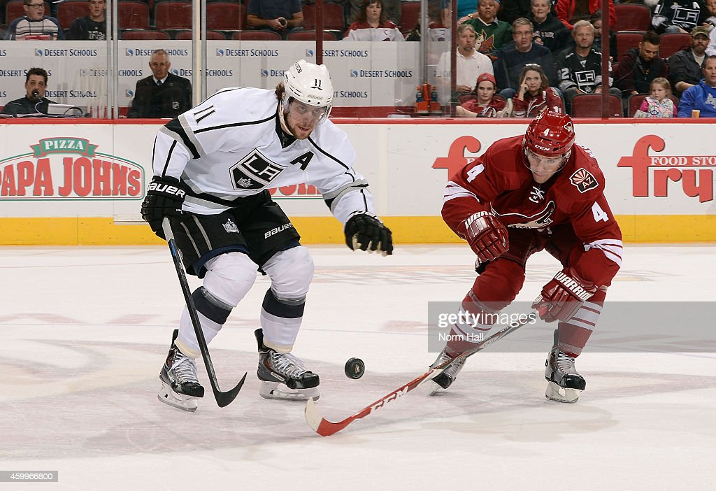 Anze Kopitar #11 of the Los Angeles Kings and Zbynek Michalek #4 of the Arizona Coyotes chase down a bouncing puck during the first period at Gila River Arena on December 4, 2014 in Glendale, Arizona.