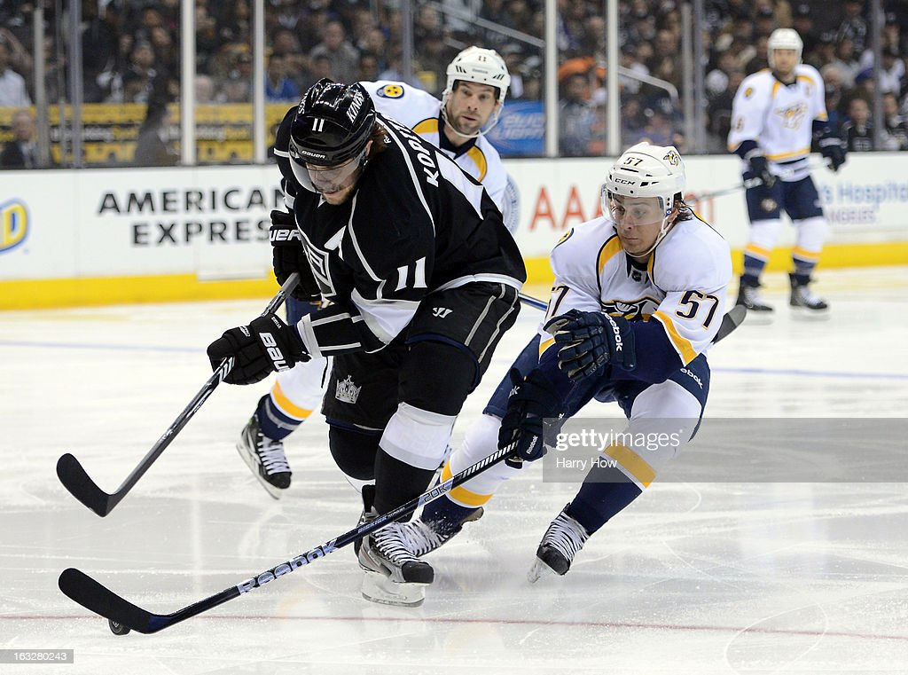 Anze Kopitar #11 of the Los Angeles Kings breaks in past Gabriel Bourque #57 and David Legwand #11 of the Nashville Predators at Staples Center on March 4, 2013 in Los Angeles, California.