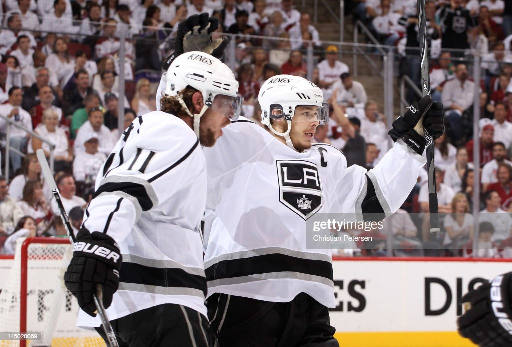 Anze Kopitar of the Los Angeles Kings celebrates with teammate Dustin Brown after Kopitar tips in a shorthanded goal in the first period on a shot by...