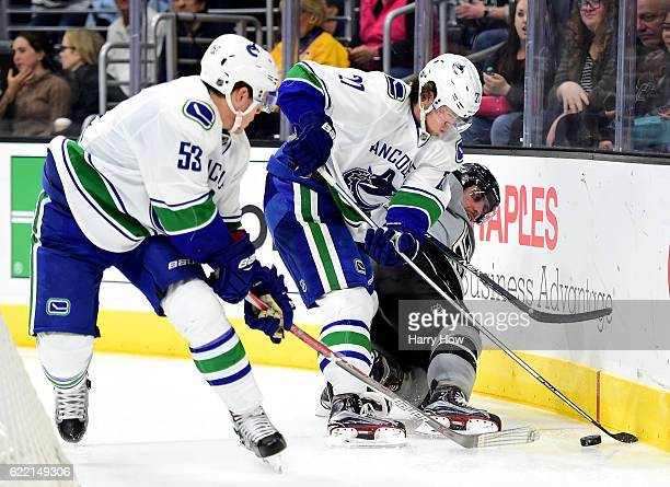Anze Kopitar of the Los Angeles Kings falls to the ice as Ben Hutton and Bo Horvat of the Vancouver Canucks take the puck at Staples Center on...